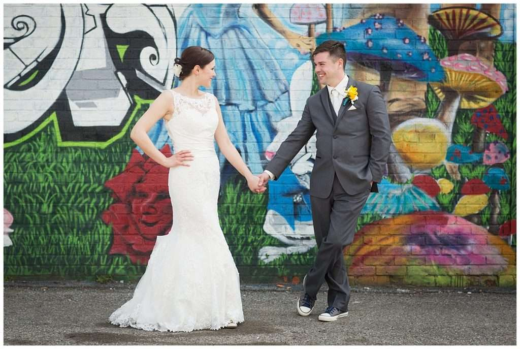 a bride and groom hold hands in front of a graffiti wall