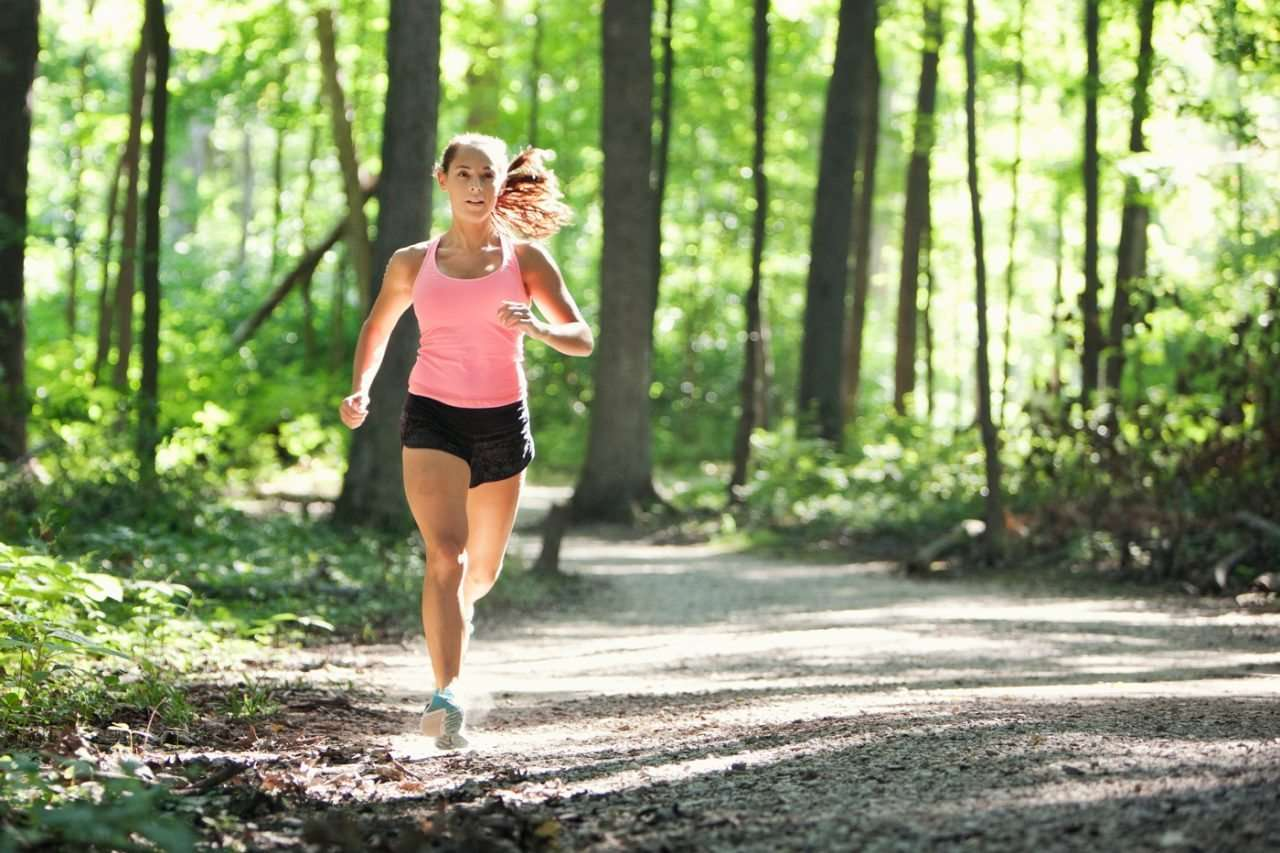 Young woman running in the woods wearing Lululemon