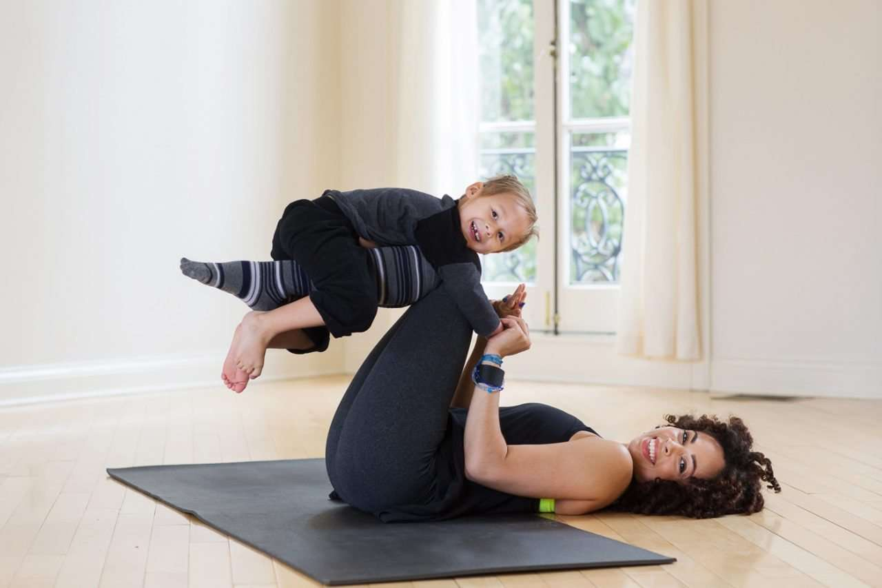 african american woman smiling and practicing yoga with her child