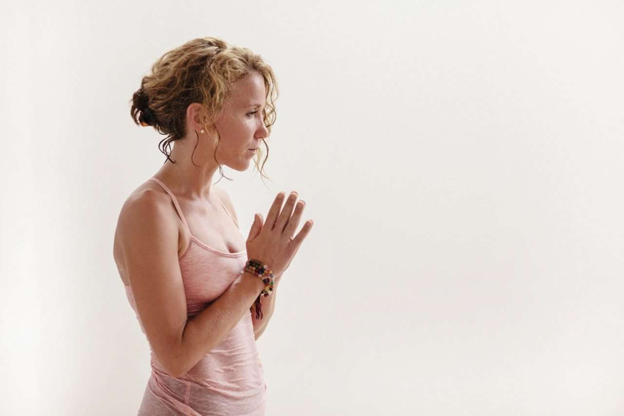 yoga instructor with hands in prayer leading a hot yoga class