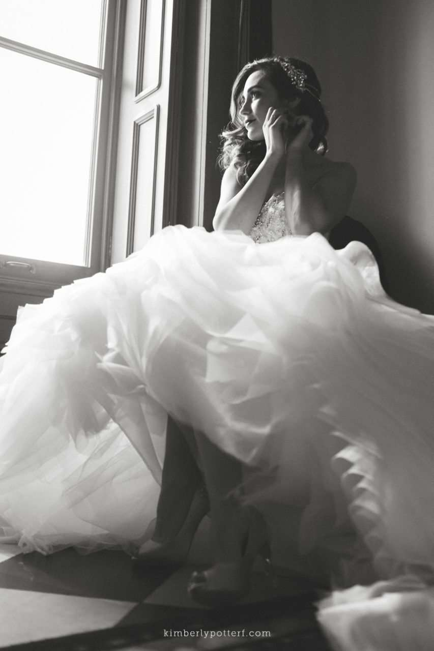 Bride wearing a ballgown sitting in window light putting on earrings
