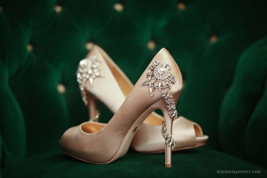 a pair of blush satin and rhinestone bridal shoes sitting on a vintage green velvet chair