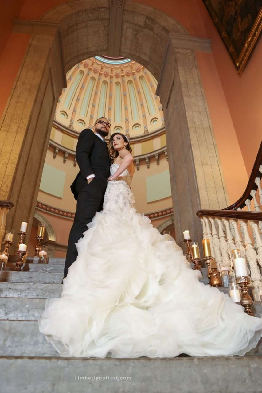 bride and groom posing together on a grand staircase lined with candles
