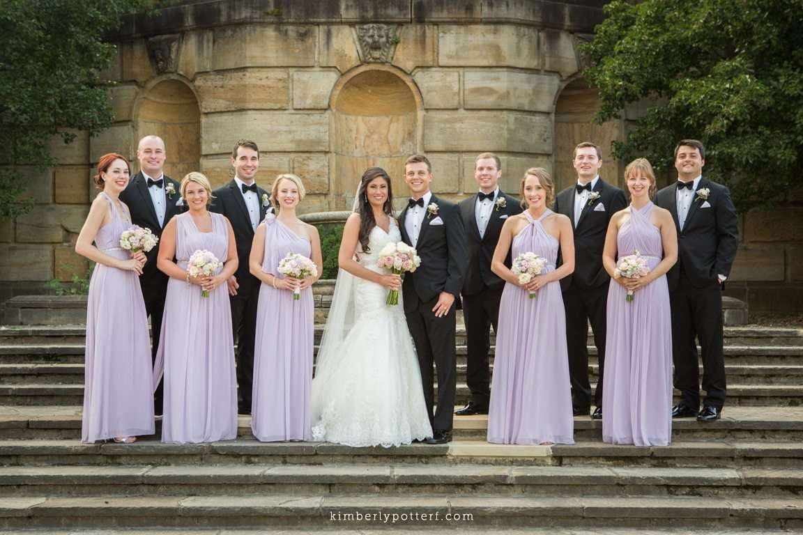 large bridal party wearing lavender dresses and classic black tuxes pose on the stone steps of the Dayton Art Institute