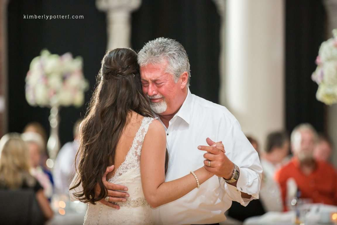 a tearful and emotional father dances with his daughter on her wedding day
