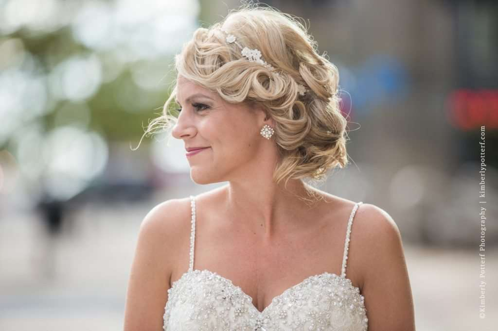 profile shot of a bride with a 1920s style updo standing in front of the Athletic Club of Columbus
