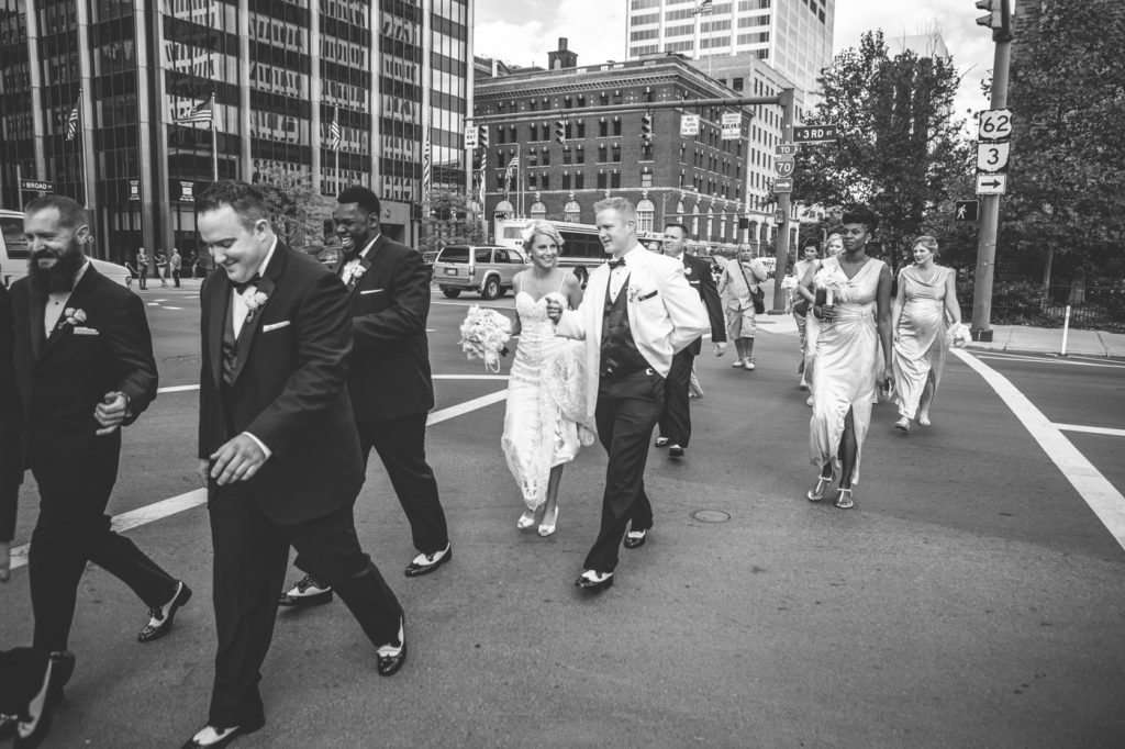 candid black and white photo of a wedding party crossing the street in downtown Columbus Ohio