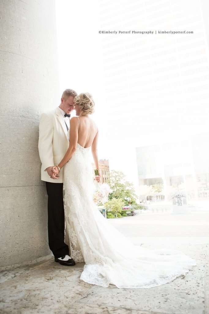 Romantic image of a bride and groom at the Ohio Statehouse, bride is wearing a low back gown