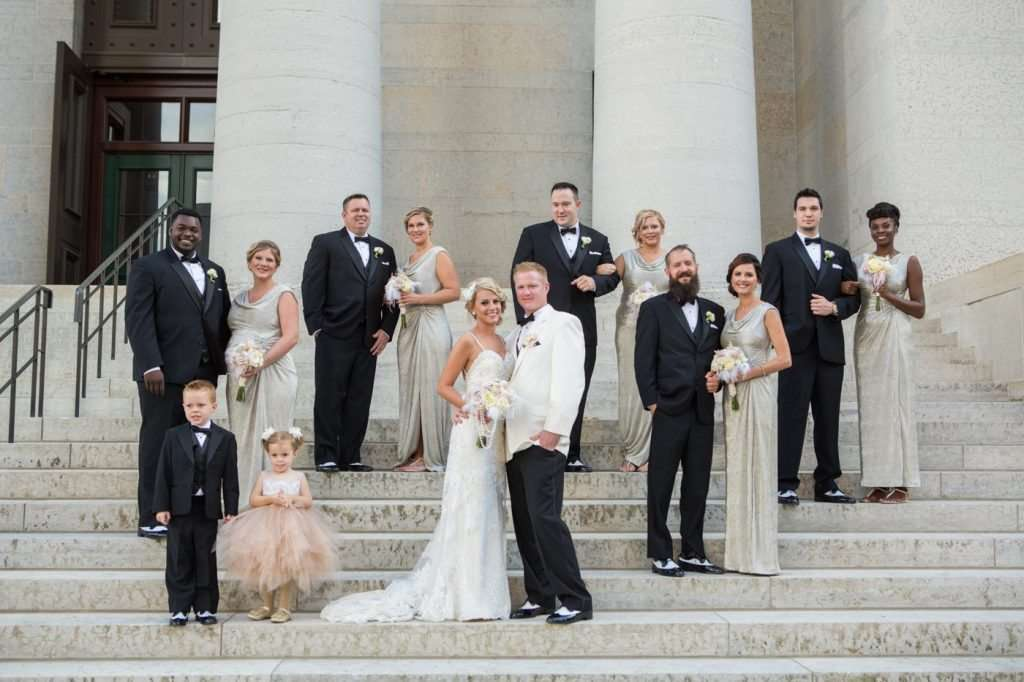 Bride and groom with their bridal party posing on the steps of the Ohio Statehouse