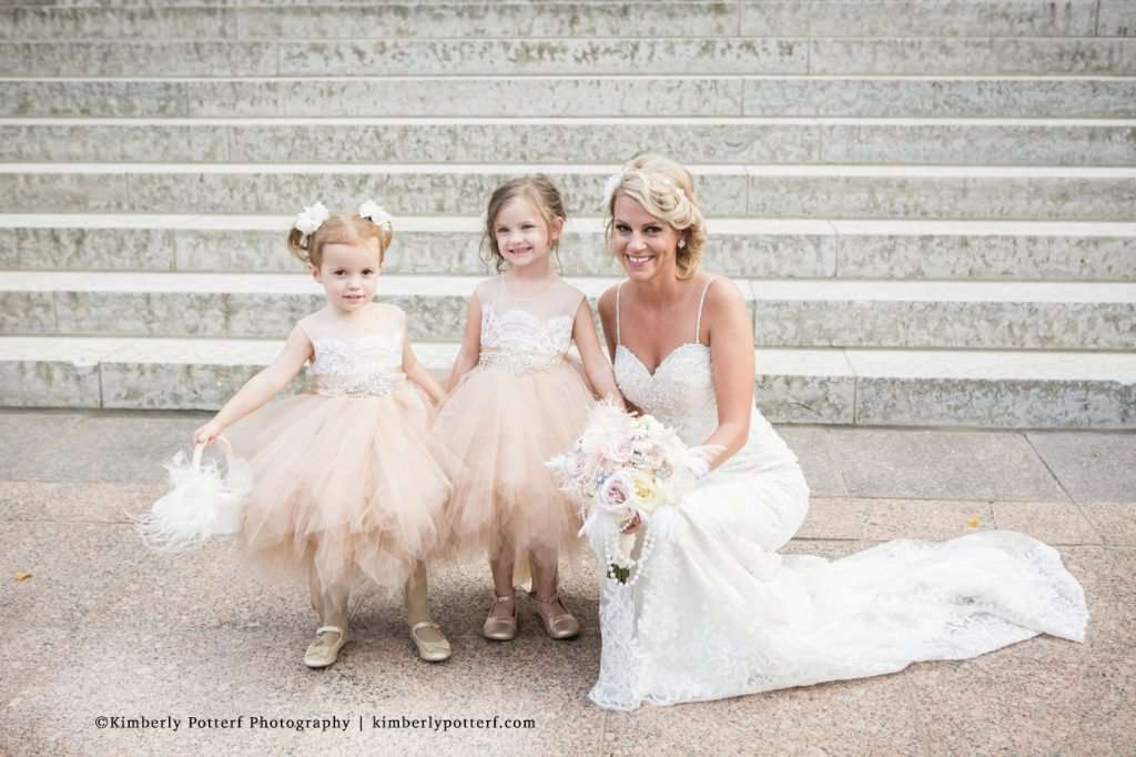 bride posing with her young flower girls