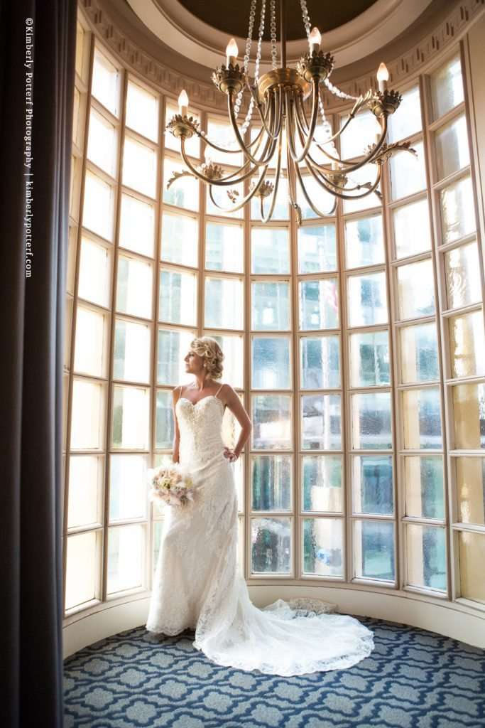 Bride posing in a large bay window at the Athletic Club of Columbus