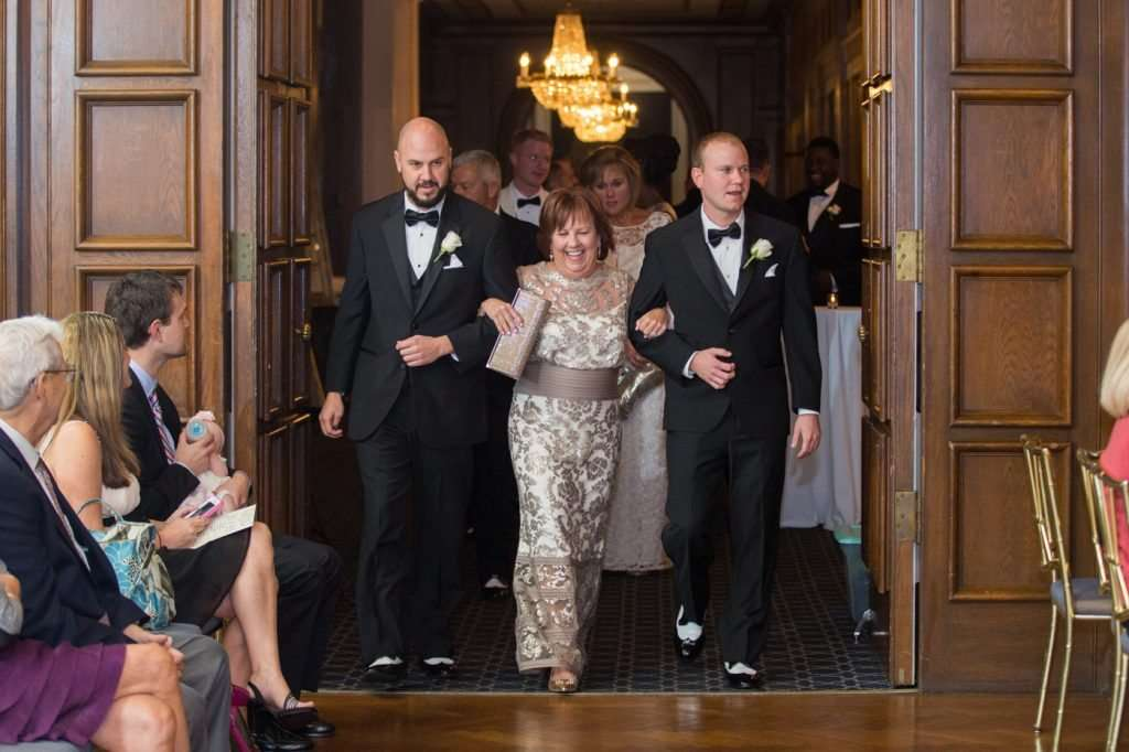 mother of the bride being escorted to her seat at a wedding ceremony