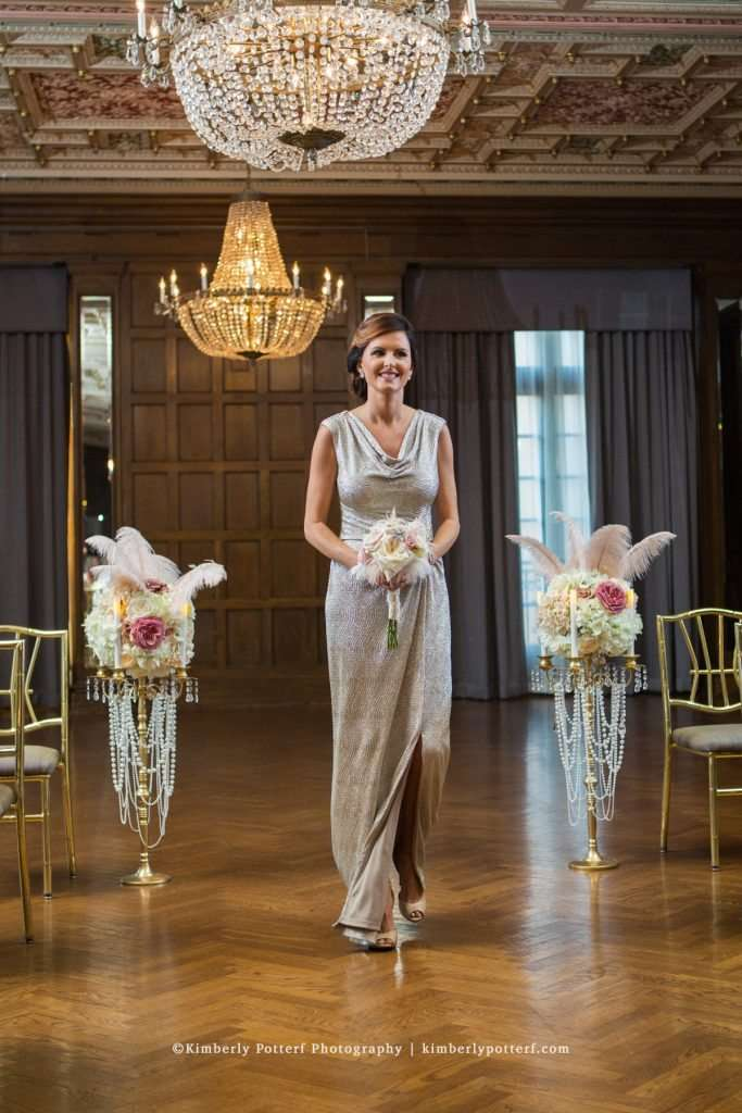 bridesmaid wearing a shimmery champagne gown walking down the aisle during a wedding ceremony in the ballroom of the Athletic Club of Columbus
