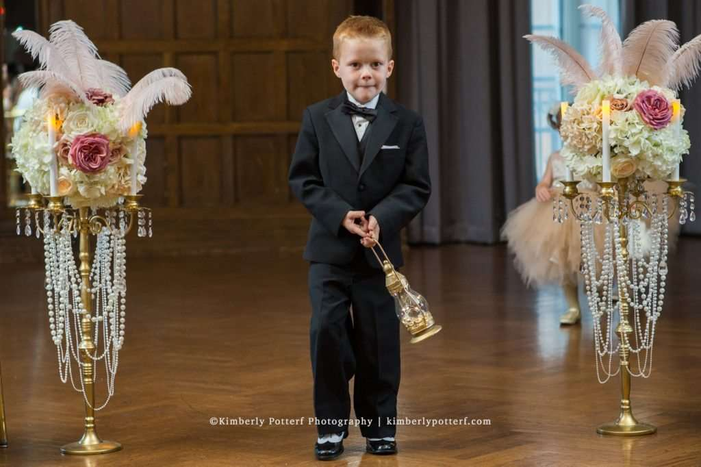 ring bearer holding a gold lantern while walking down the aisle during the ceremony