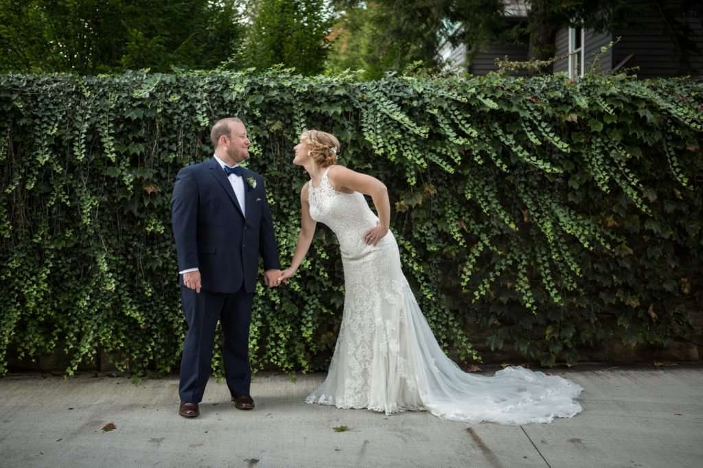 a bride playfully smiles at her groom as they hold hands standing in front of a wall of ivy