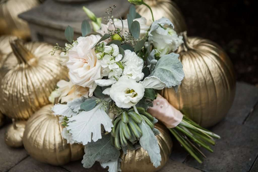 fall wedding decor with gold pumpkins and bridal bouquet