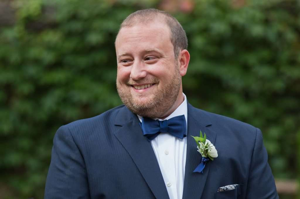 Groom wearing a dark blue suit with a bowtie smiles during his wedding ceremony