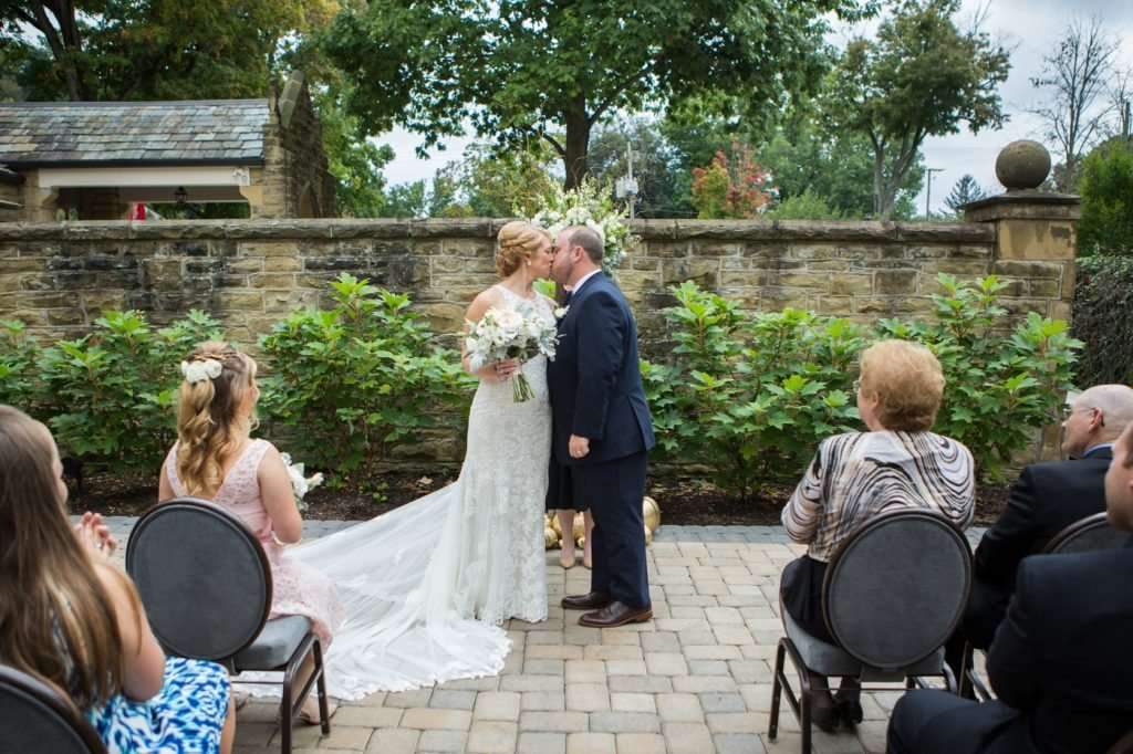 Bride and groom first kiss during their wedding ceremony at the Granville Inn