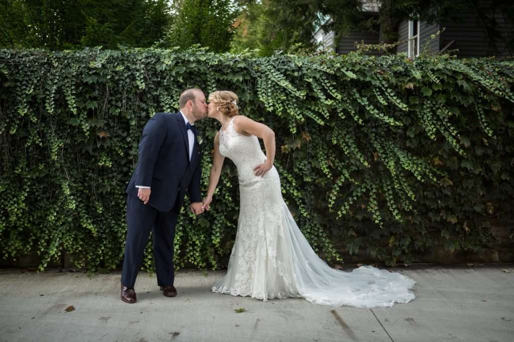 playful image of a bride and groom kissing in front of a wall of ivy at the Granville Inn in Ohio
