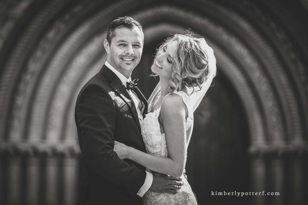 Black and white image of bride and groom hugging and smiling in front of the Bluestone wedding venue in downtown Columbus