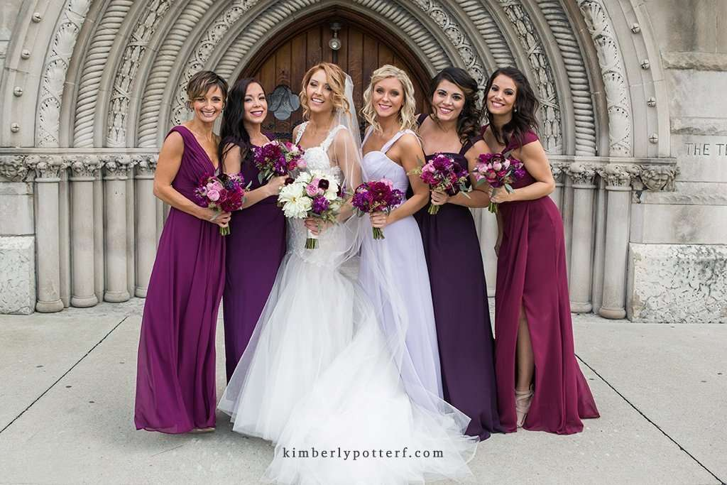 Bridal party wearing purple and fuchsia dresses in front of the Bluestone wedding venue
