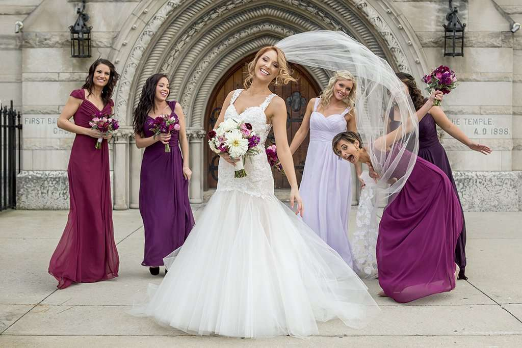 Fun casual shot of a bride goofing around and laughing with her bridesmaids, her veil is blowing in the wind