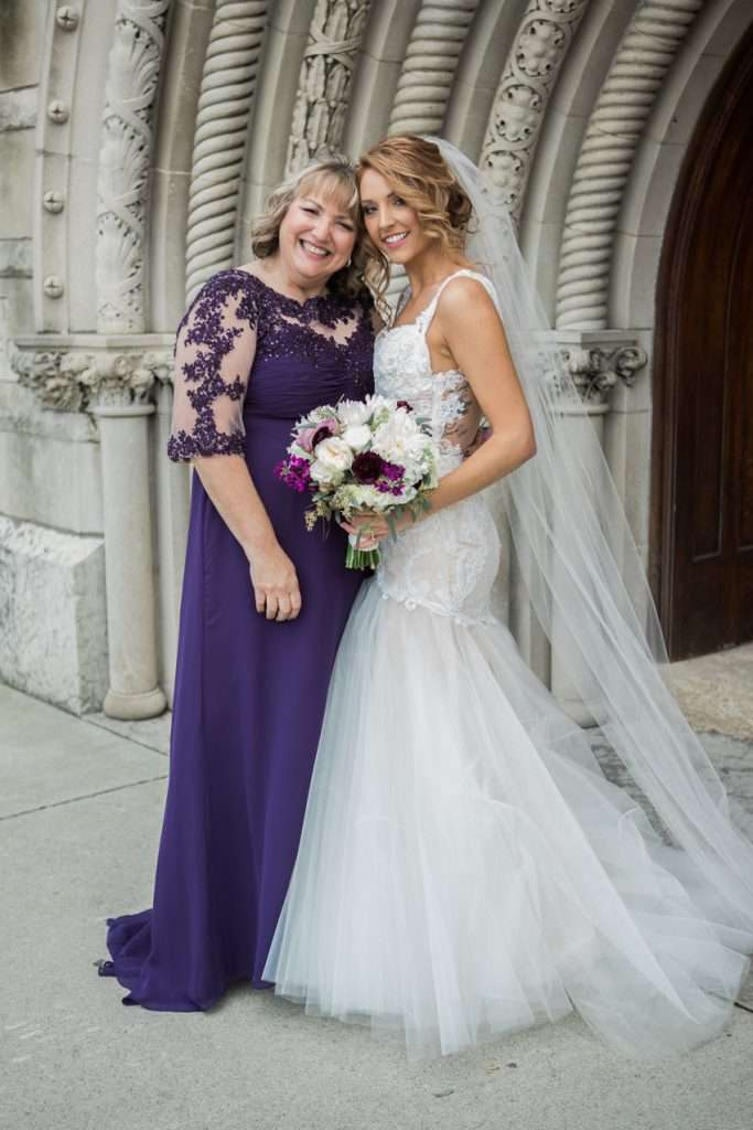 Mother of the bride wearing a long purple gown poses with her daughter on her wedding day