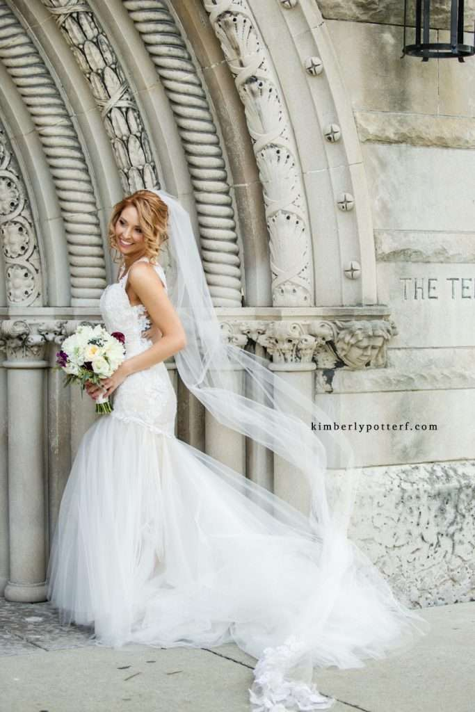 Bride posing in the Giselle by WToo wedding gown in front of the Bluestone event venue, veil blowing in the wind