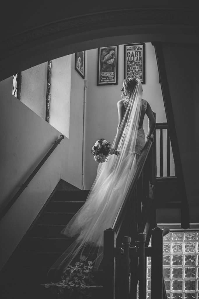 dramatic black and white portrait of a bride on the steps inside the Bluestone with window light