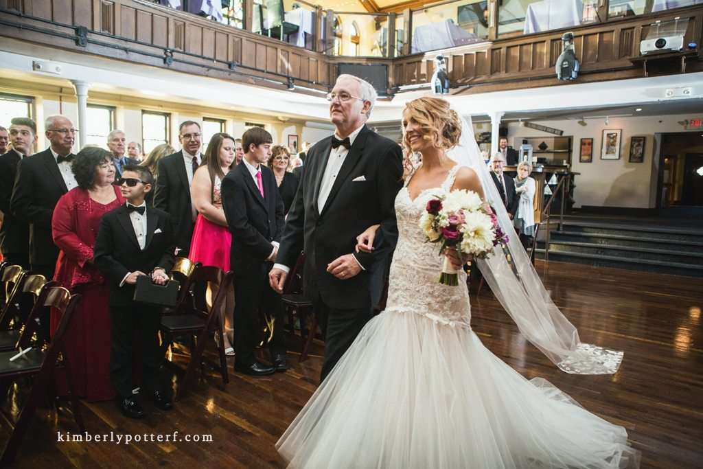 a happy bride walks down the aisle with her father during a wedding ceremony at the Bluestone in Columbus Ohio
