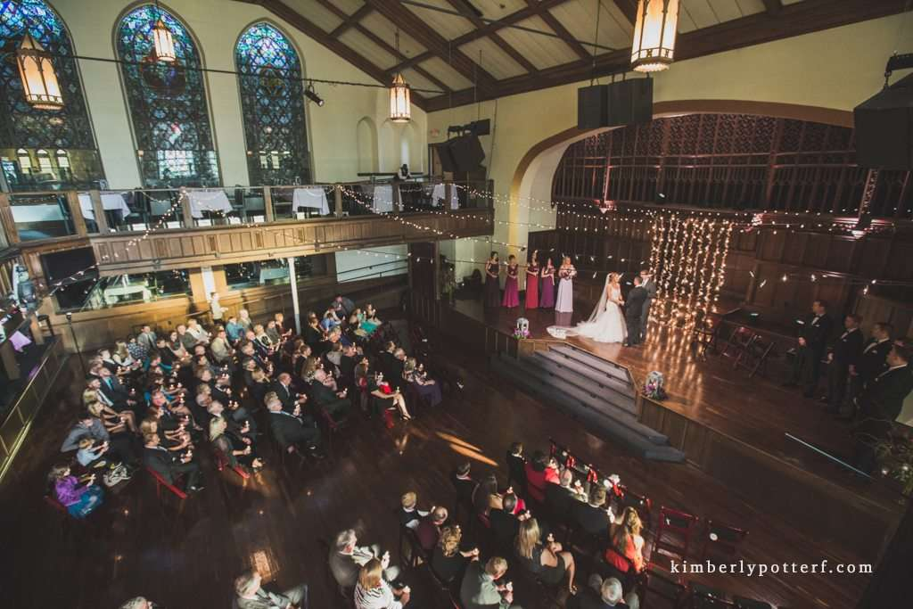 dramatic wide angle image of a wedding ceremony at the Bluestone event venue in Columbus Ohio showcasing the large stained glass windows