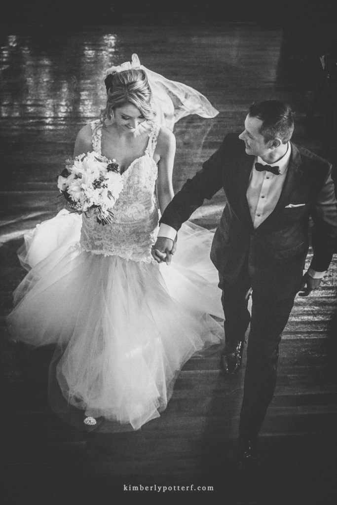 dramatic overhead view of a bride and groom walking