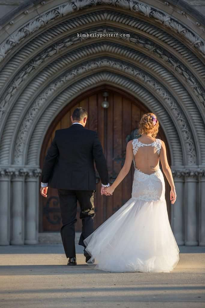 bride and groom holding hands and walking into the Bluestone event venue at sunset