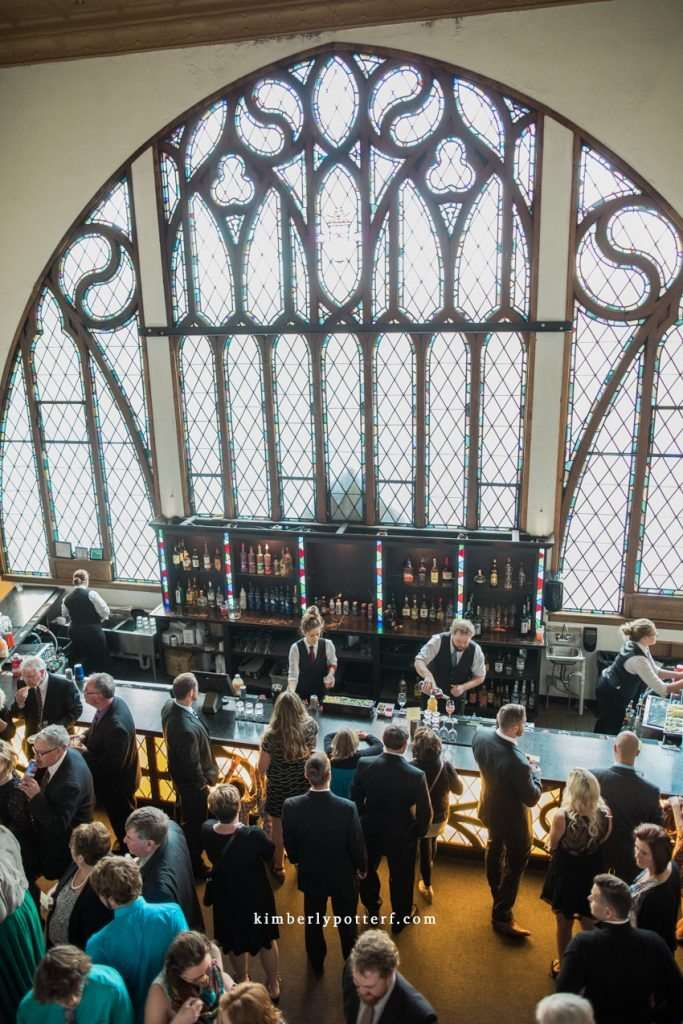 wide angle view of the large stained glass windows in the cocktail hour space at the Bluestone wedding venue