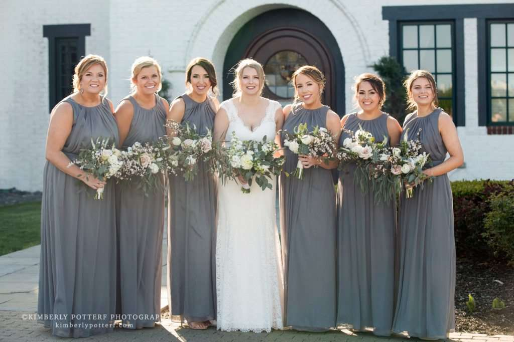 A bride with her bridesmaids holding neutral colored bouquets in front of the Golf Club of Dublin