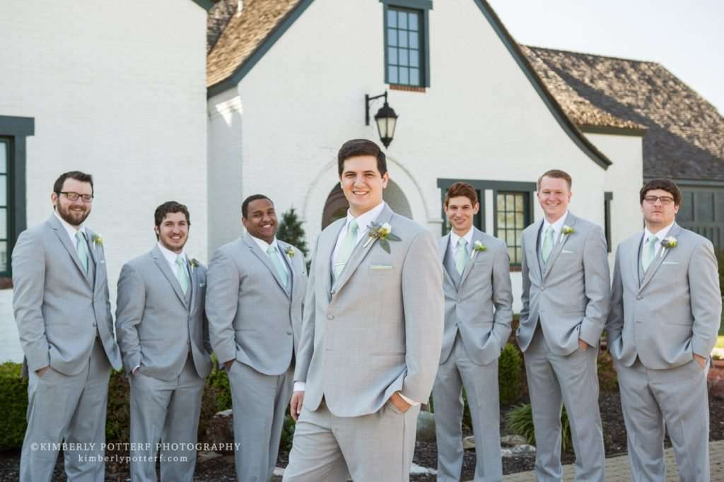 A groom with his groomsmen wearing light gray suits standing in front of the Golf Club of Dublin