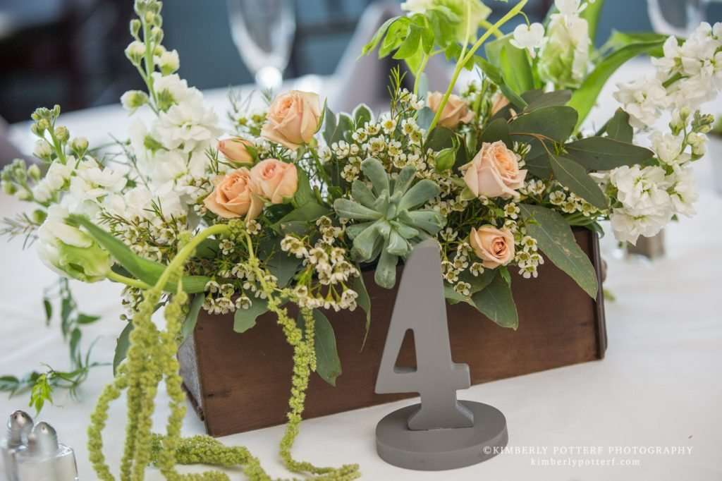 close up detail of rustic floral centerpieces with succulents and peach roses and a table number