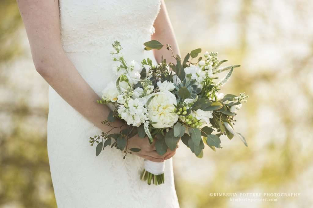 close up of a bride holding her bouquet made up of white flowers and lush greenery by Madison House Designs