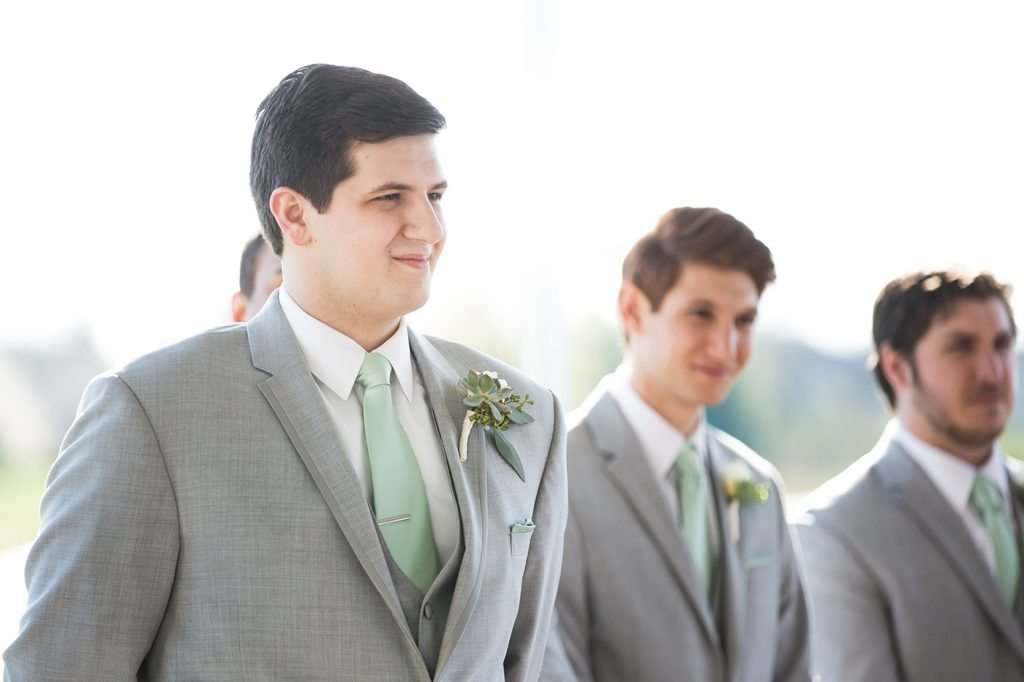 candid image of a groom smiling and watching his bride walk down the aisle