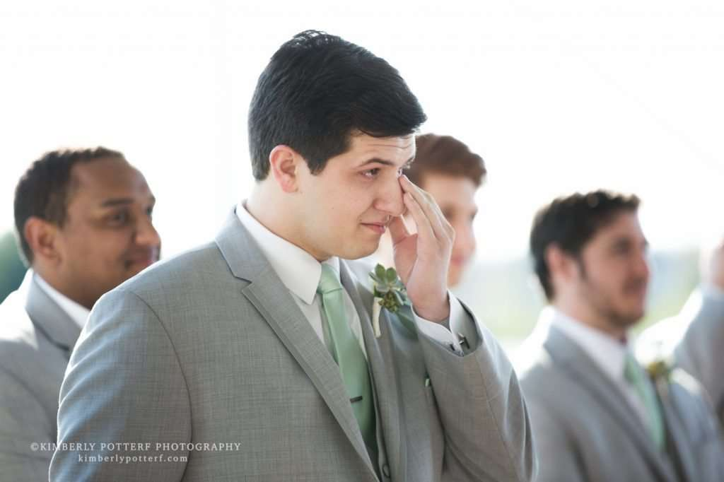 a groom wiping tears from his eyes as he watches his bride walk down the aisle