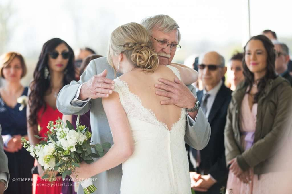 a father hugs his daughter during a wedding ceremony
