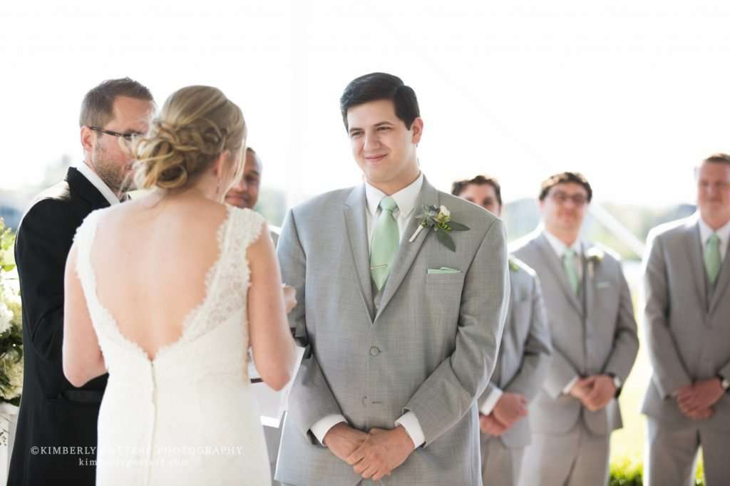 a groom smiling and listening to his wife speak her vows during a wedding ceremony