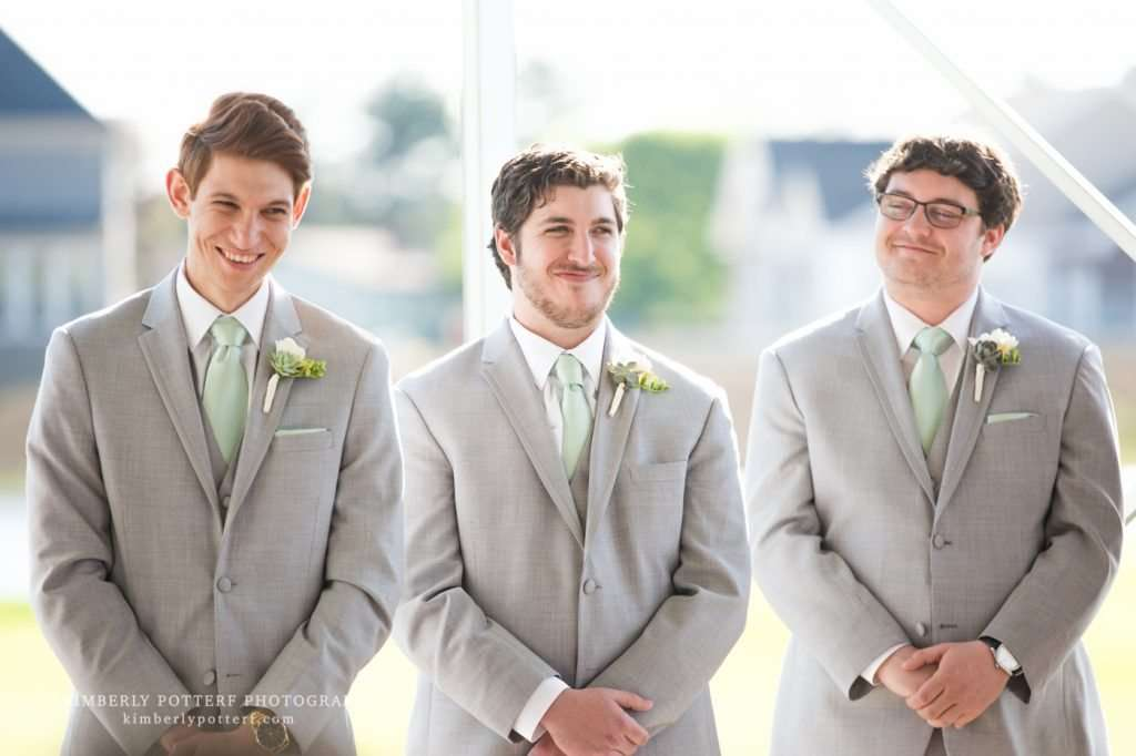 candid shot of groomsmen laughing during an outdoor wedding ceremony