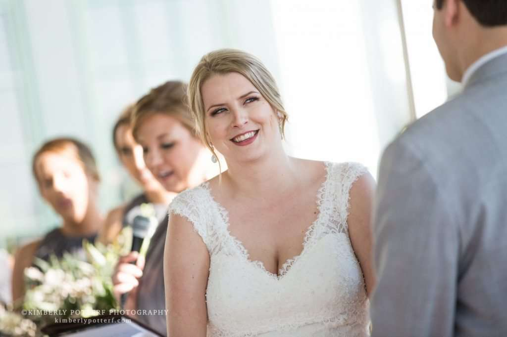 a bride smiles at her groom during an outdoor wedding ceremony