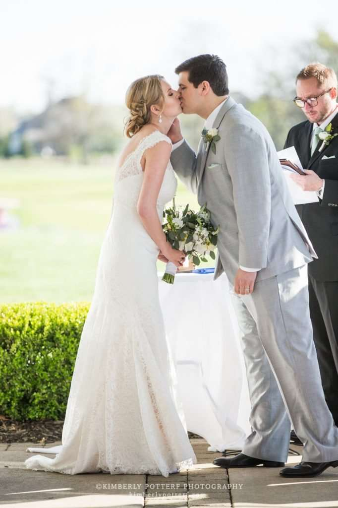 a bride and groom exchange their first kiss as husband and wife