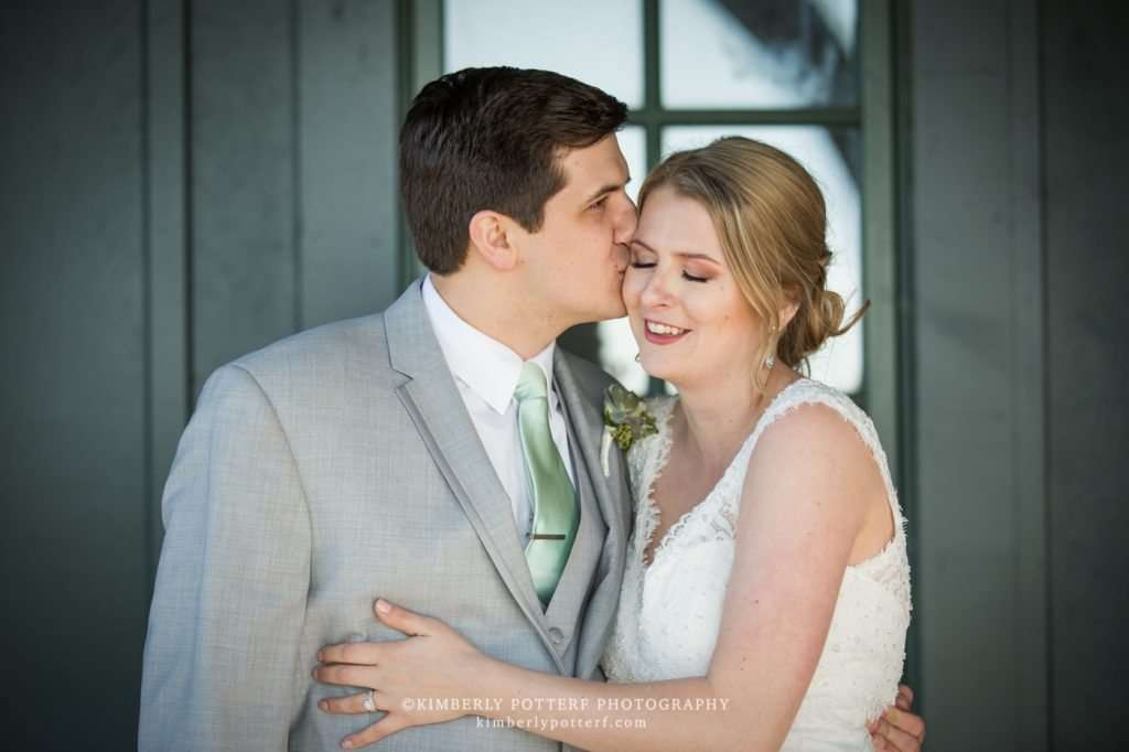 a newly wedded bride and groom enjoy a quiet moment right after their ceremony as the groom kisses her cheek