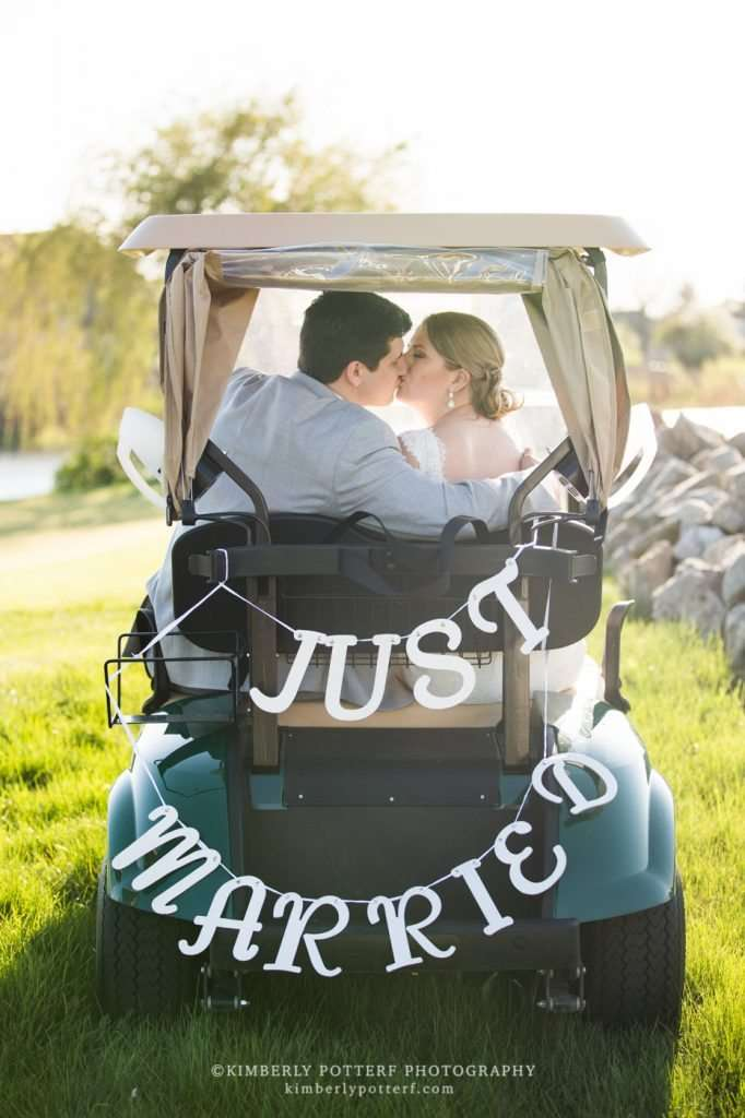a bride and groom kiss on a getaway golf cart with a Just Married sign on the back