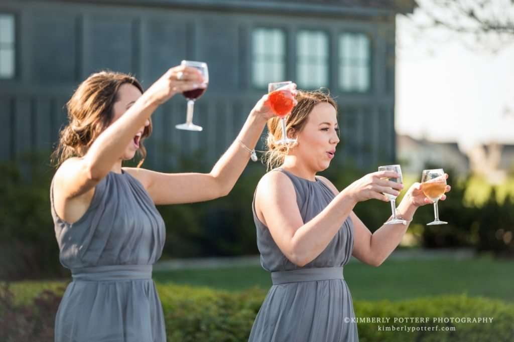 bridesmaids carrying wine glasses cheers to the new couple