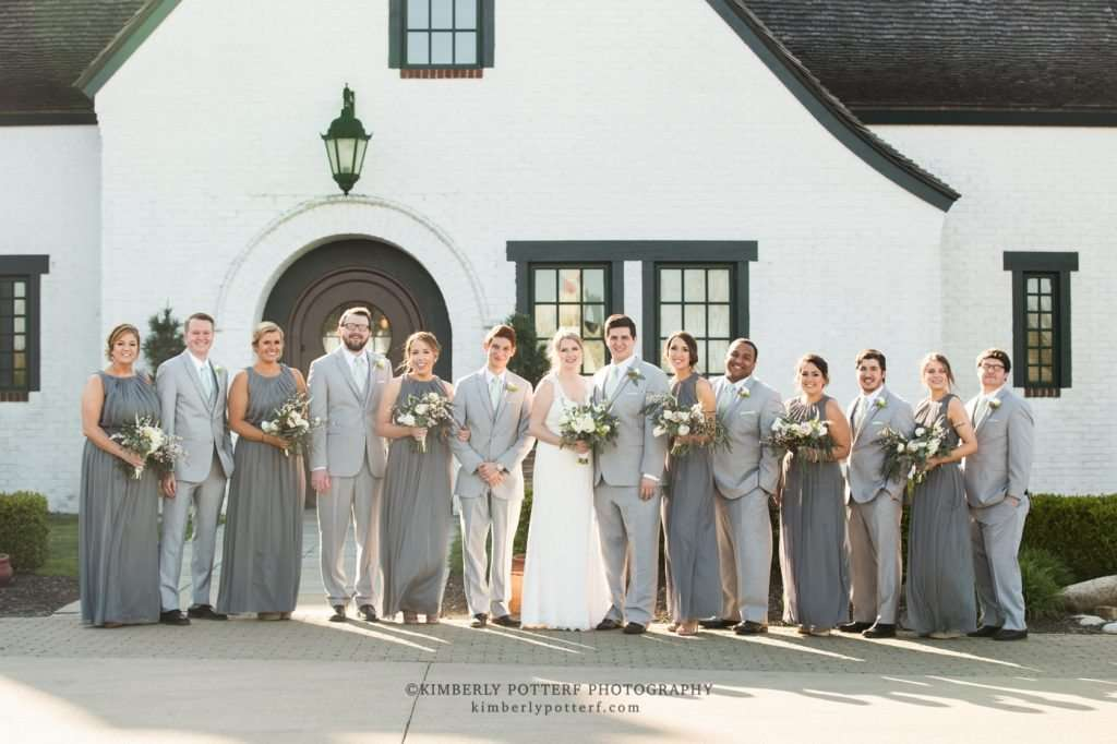 group shot of a large bridal party wearing light gray suits and dresses in front of the Golf Club of Dublin at sunset
