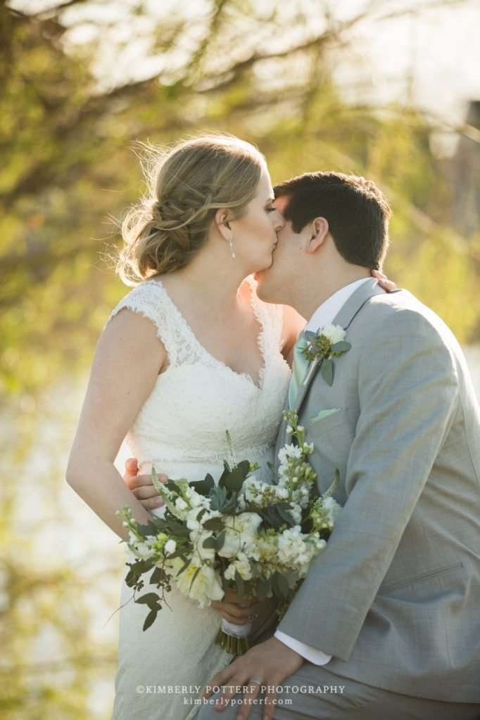 a bride kisses her groom on the cheek at sunset in front of willow trees